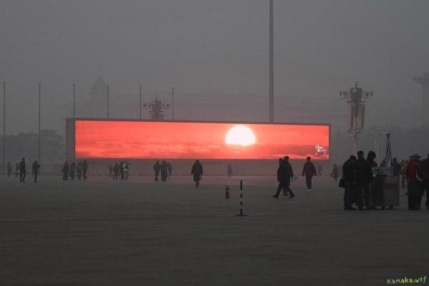 В Пекине забили на попытки бороться со смогом и просто транслируют фейковый закат по огромному экрану.